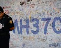 Malaysia airport police officer stands in front of messages board for the passengers aboard a missing Malaysia Airlines plane at Kuala Lumpur International Airport in Sepang, Malaysia, Wednesday, March 19, 2014. New radar data from Thailand gave Malaysian investigators more potential clues Wednesday for how to retrace the course of the missing Malaysian airliner, while a massive multinational search unfolded in an area the size of Australia.