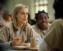 "FILE - This image released by Netflix shows Taylor Schilling, left, and Uzo Aduba in a scene from ""Orange Is the New Black."" Season two debuts on Netflix on June 6, 2014."